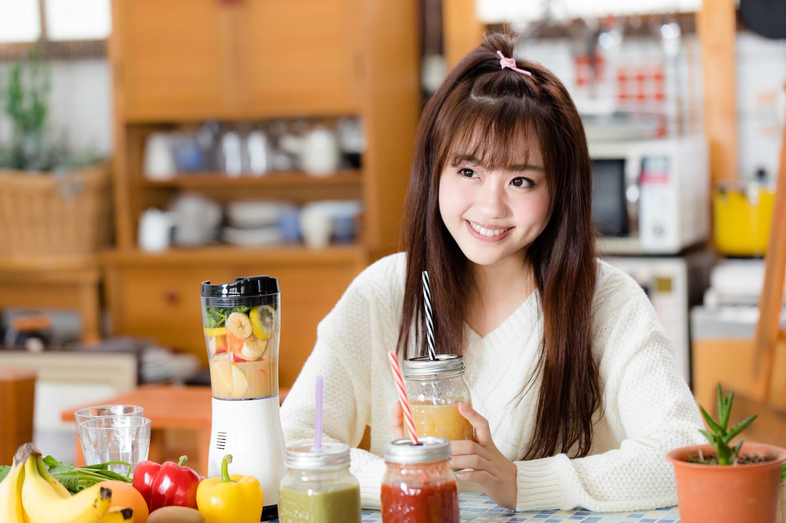「台所でスムージーを飲む女性」の写真[モデル:河村友歌]